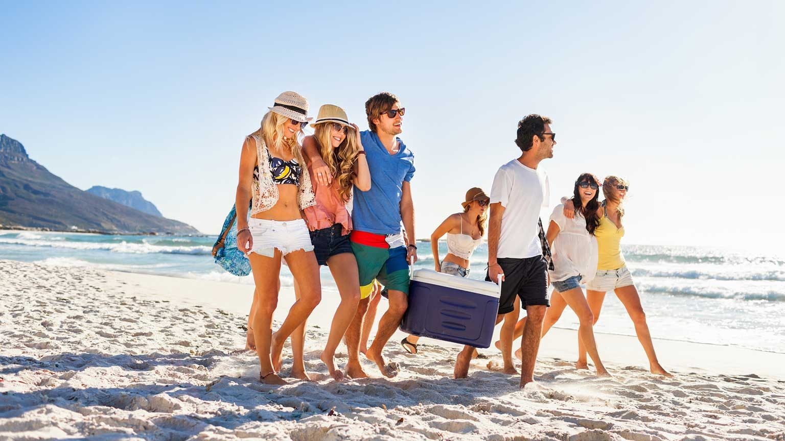 Group of friends on spring break at the beach carrying a cooler for a party