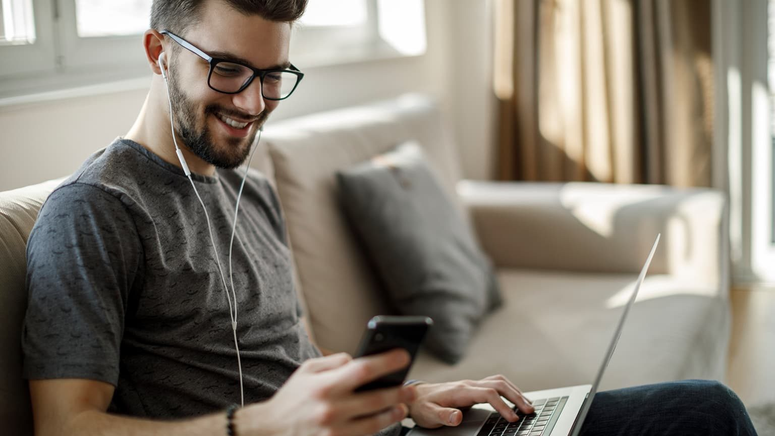 Young man using social media at home with laptop and mobile phone