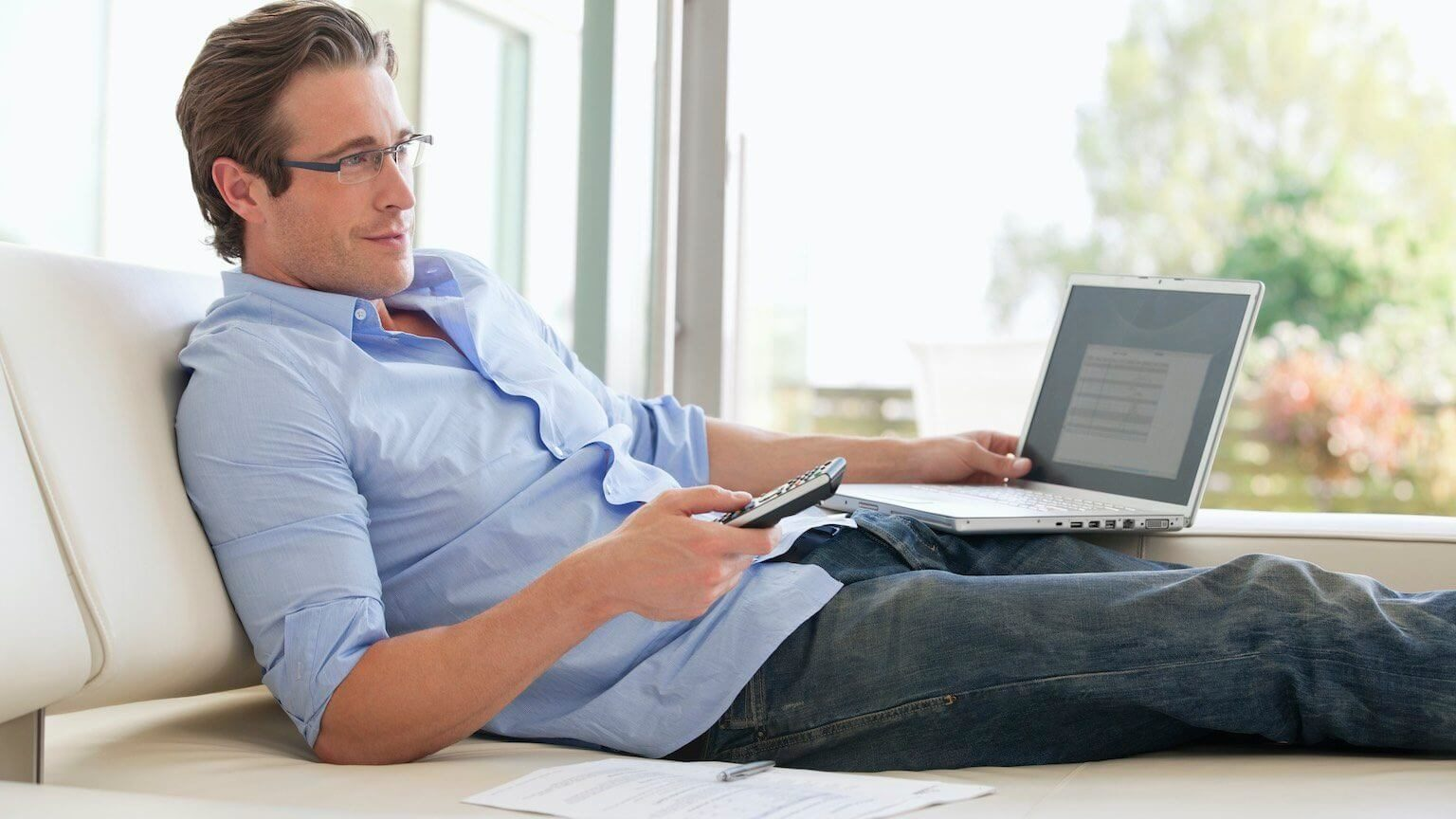 Man watching TV while working on his laptop