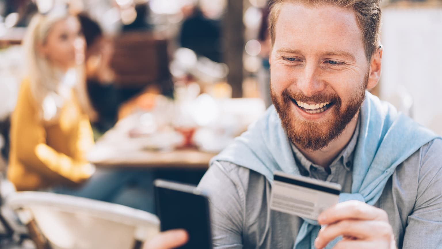 Young man online banking outdoor in cafe