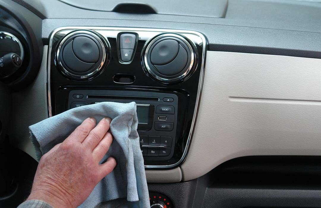 Man cleaning panel in auto