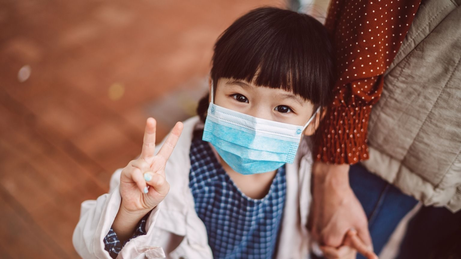 Little girl wearing face mask making peace sign