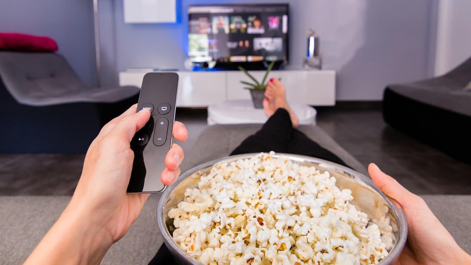 woman watching tv while eating popcorn