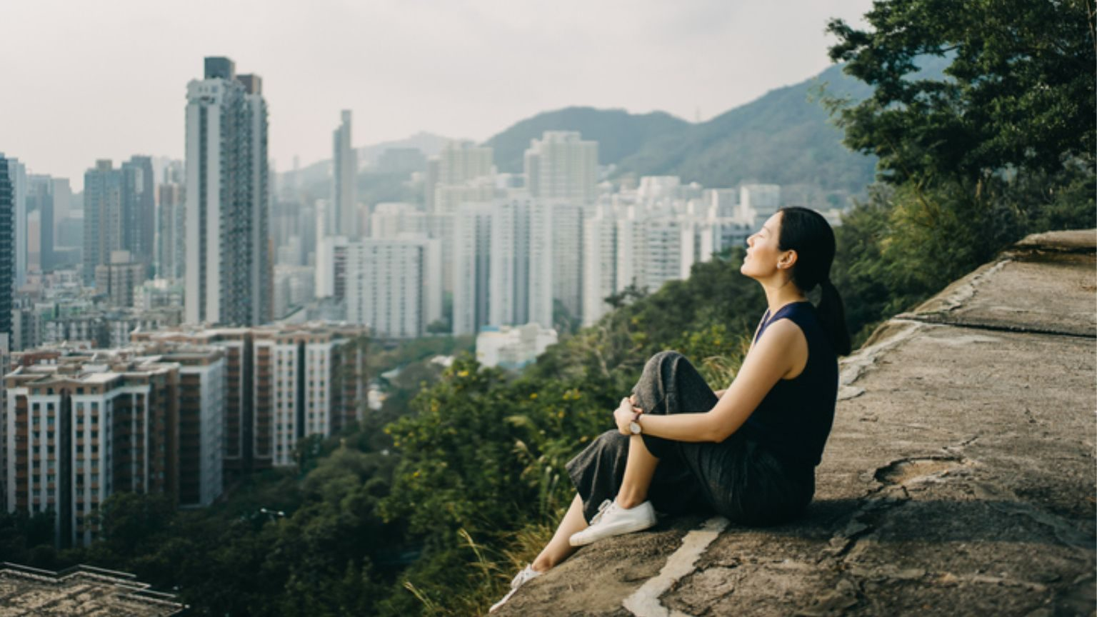 Young woman with eyes closed enjoying the tranquility and the spectacular city skyline on the top of mountain