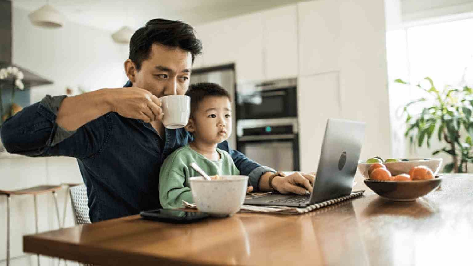 Father working from home with young son at kitchen table