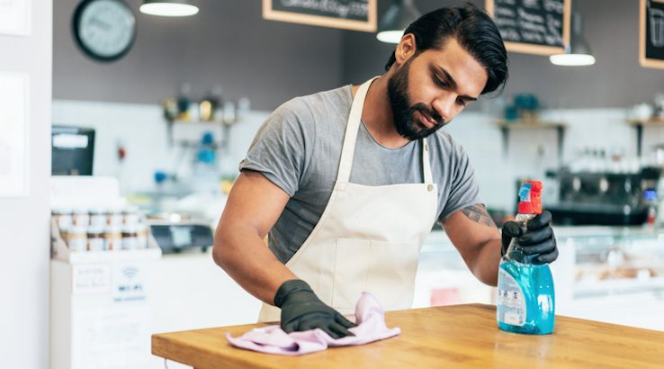 Business owner cleaning with spray disinfectant and gloves in cafe.