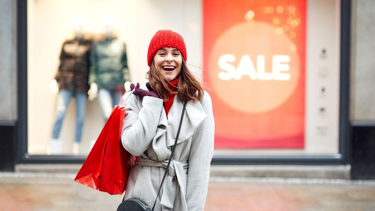 Woman smiling with shopping bags in hand
