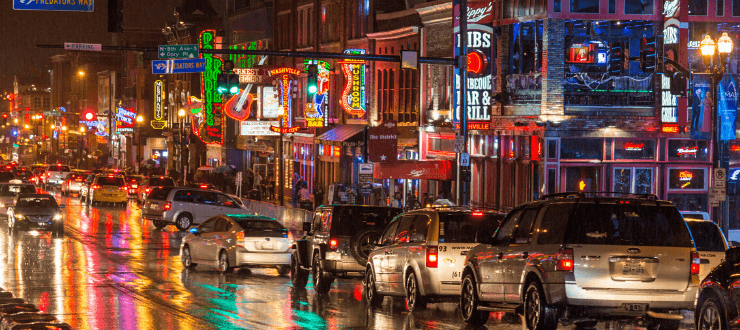 Neon signs, reflections, and a line of traffic is reflected on wet streets during a rainstorm in Nashville's downtown honky tonk music district on Broadway Street