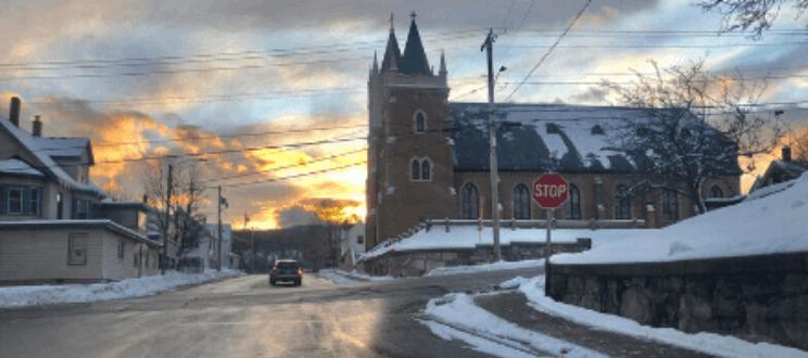 Car driving down street in Rumford, Maine near church during winter - stock photo