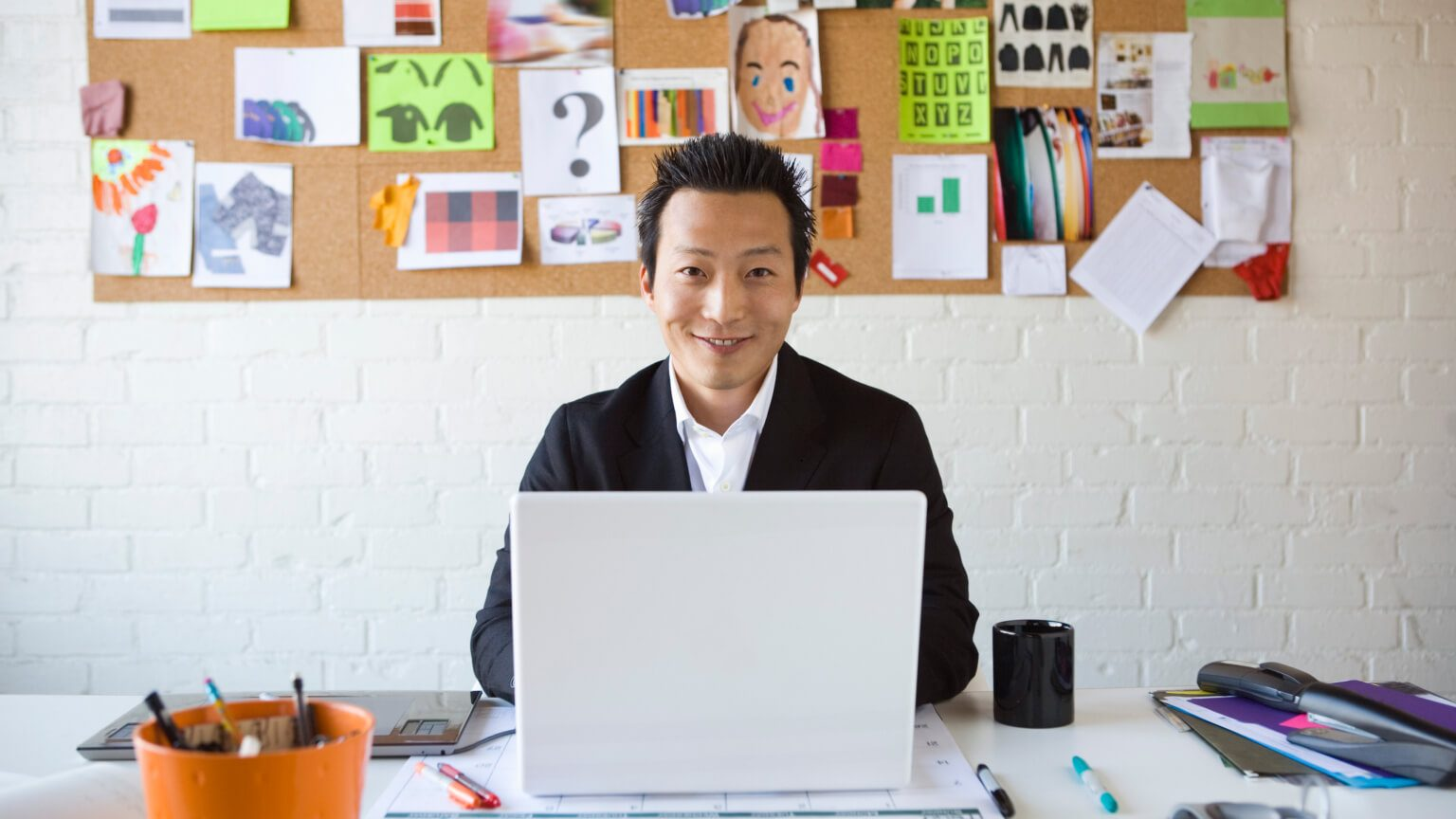 Asian man sitting in front of laptop with image board in the background