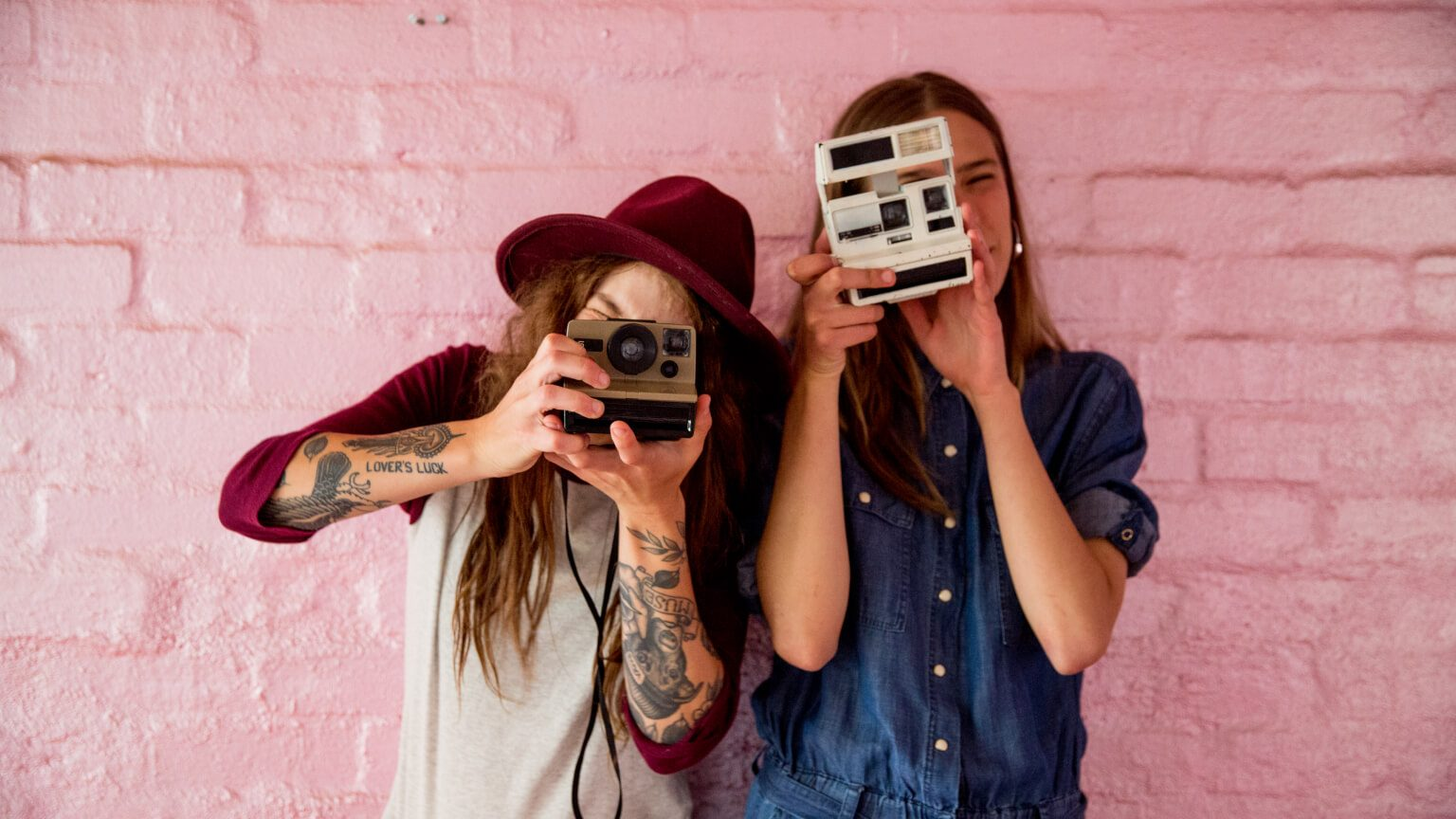 Two young women taking pictures with a polaroid