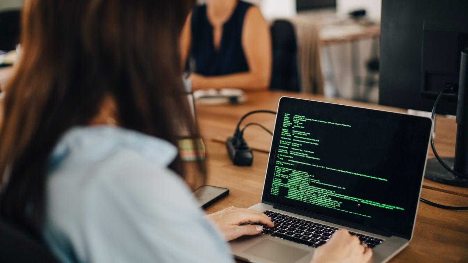 Woman sitting at laptop looking at typing programming language