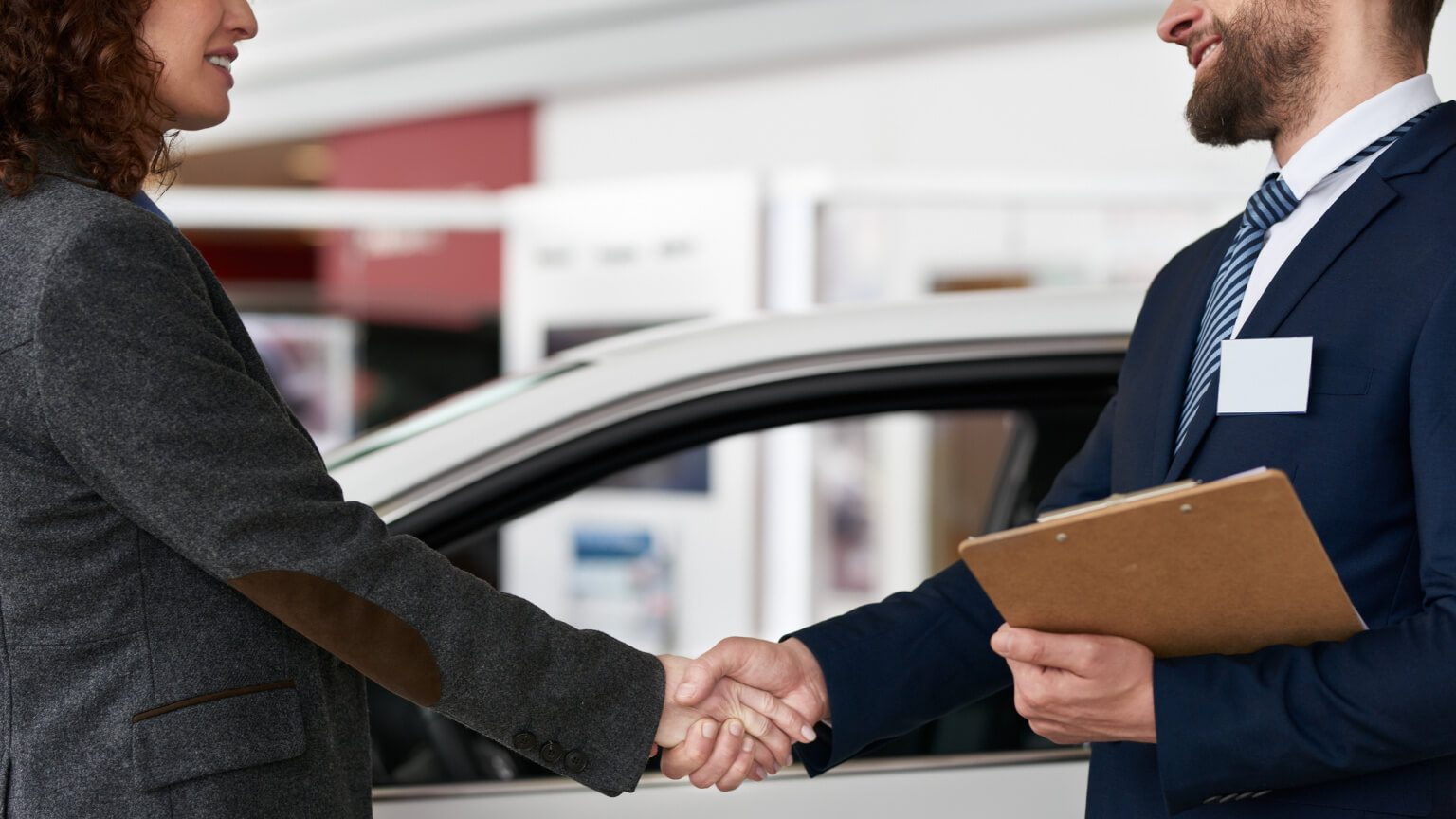 Two people shaking hands at an auto dealership