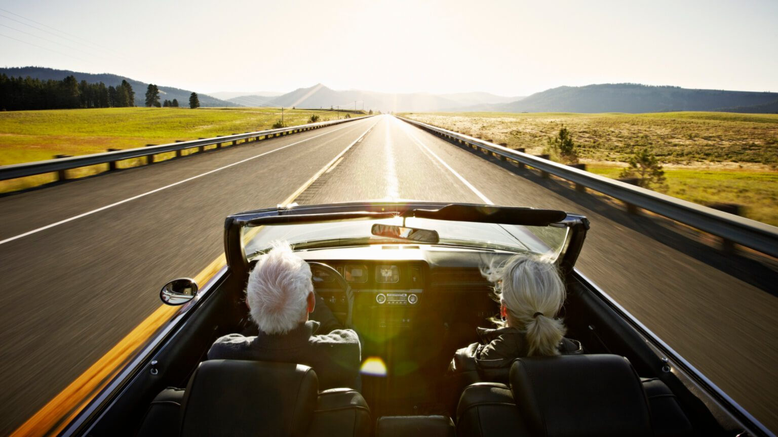 two seniors driving in a convertible on an open road