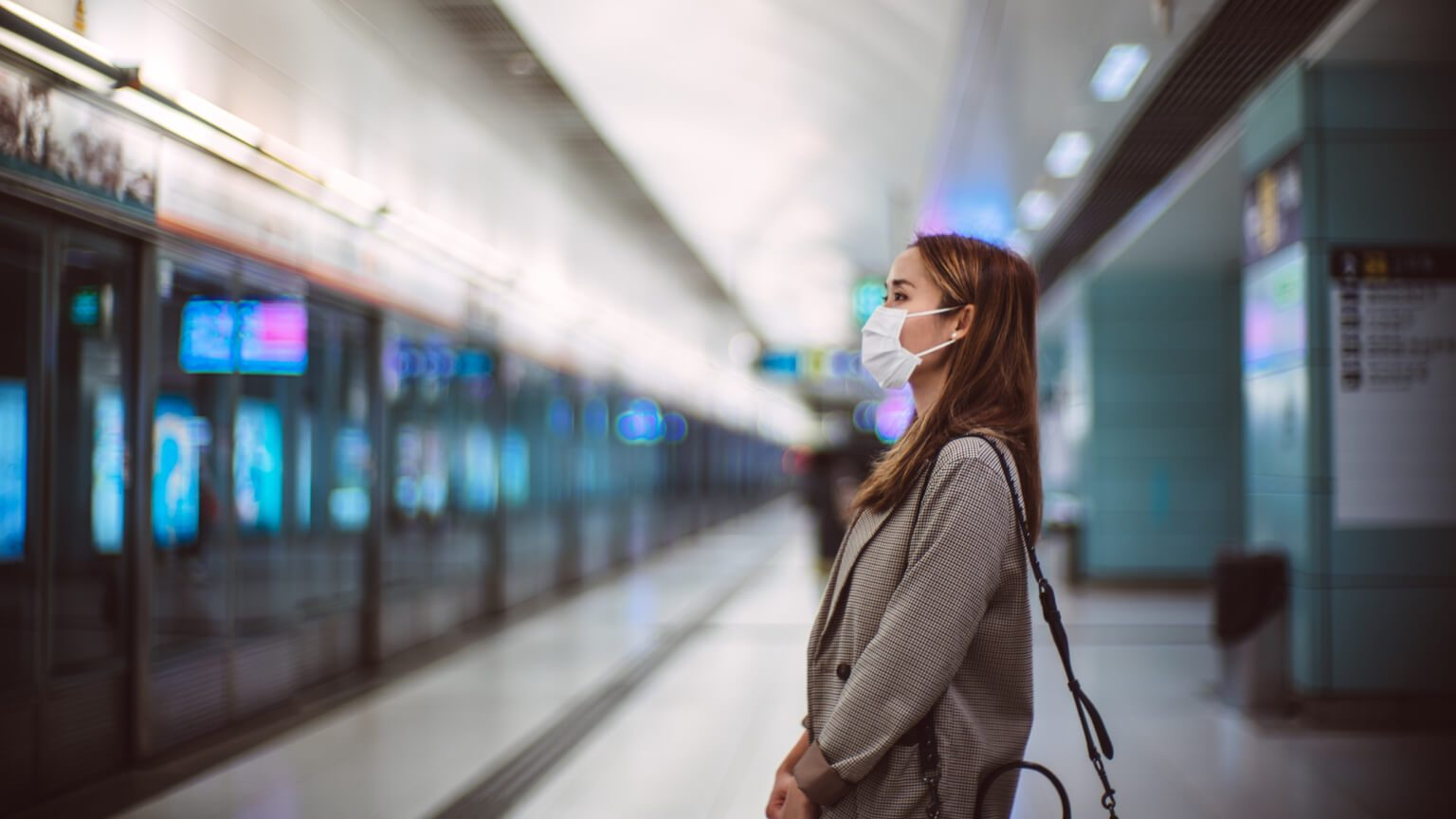 woman standing in the airport with a mask on