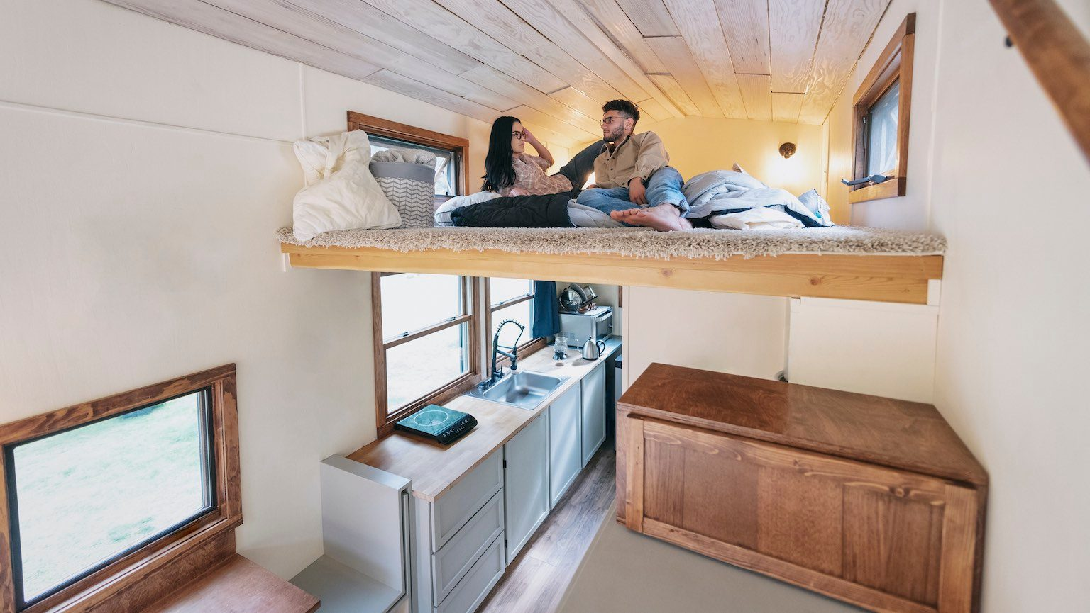 Young couple relaxing in the loft bed of a tiny house.