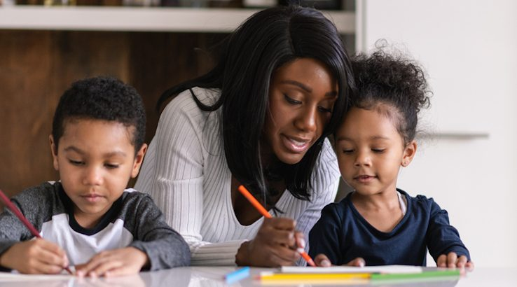 Mom helping her two children with homeschool work.