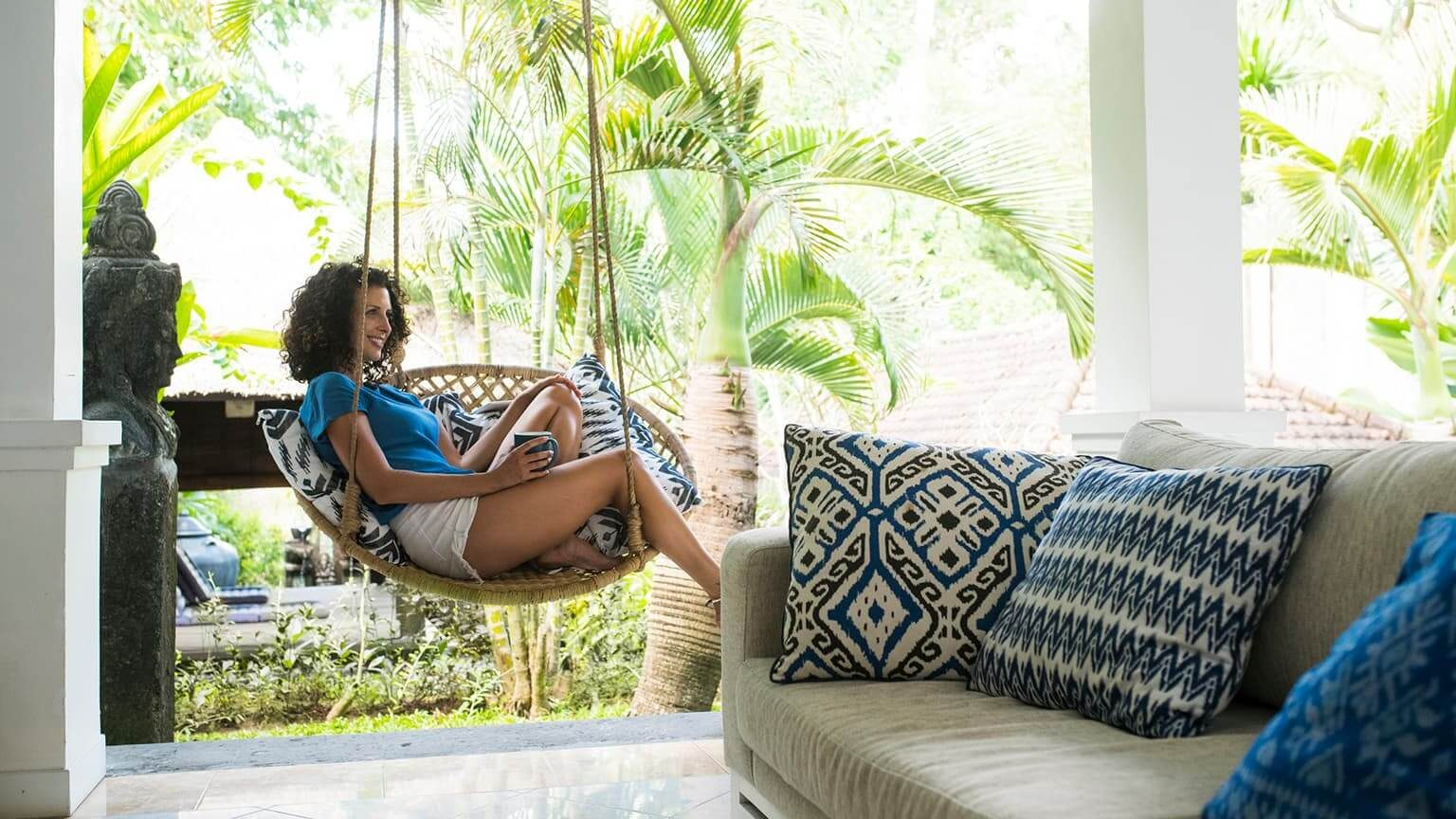 Smiling woman relaxing in hanging chair, in vacation home