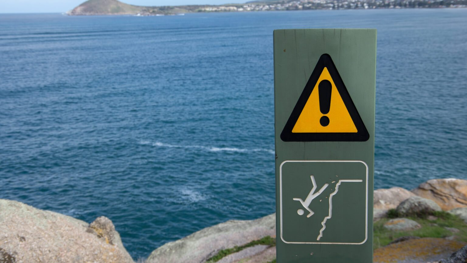 Caution sign with a drawing of a person falling of a cliff below