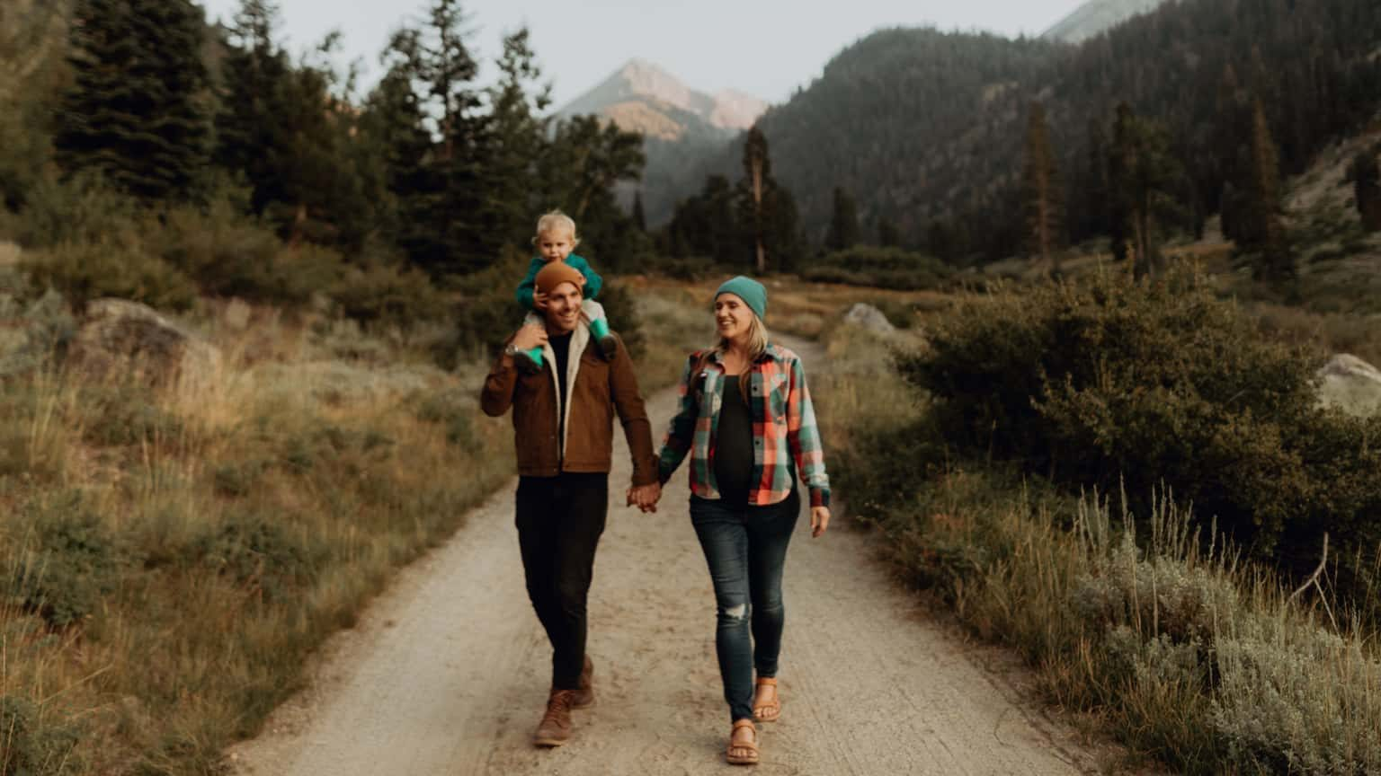 Couple walking with young child on hiking path in national park.