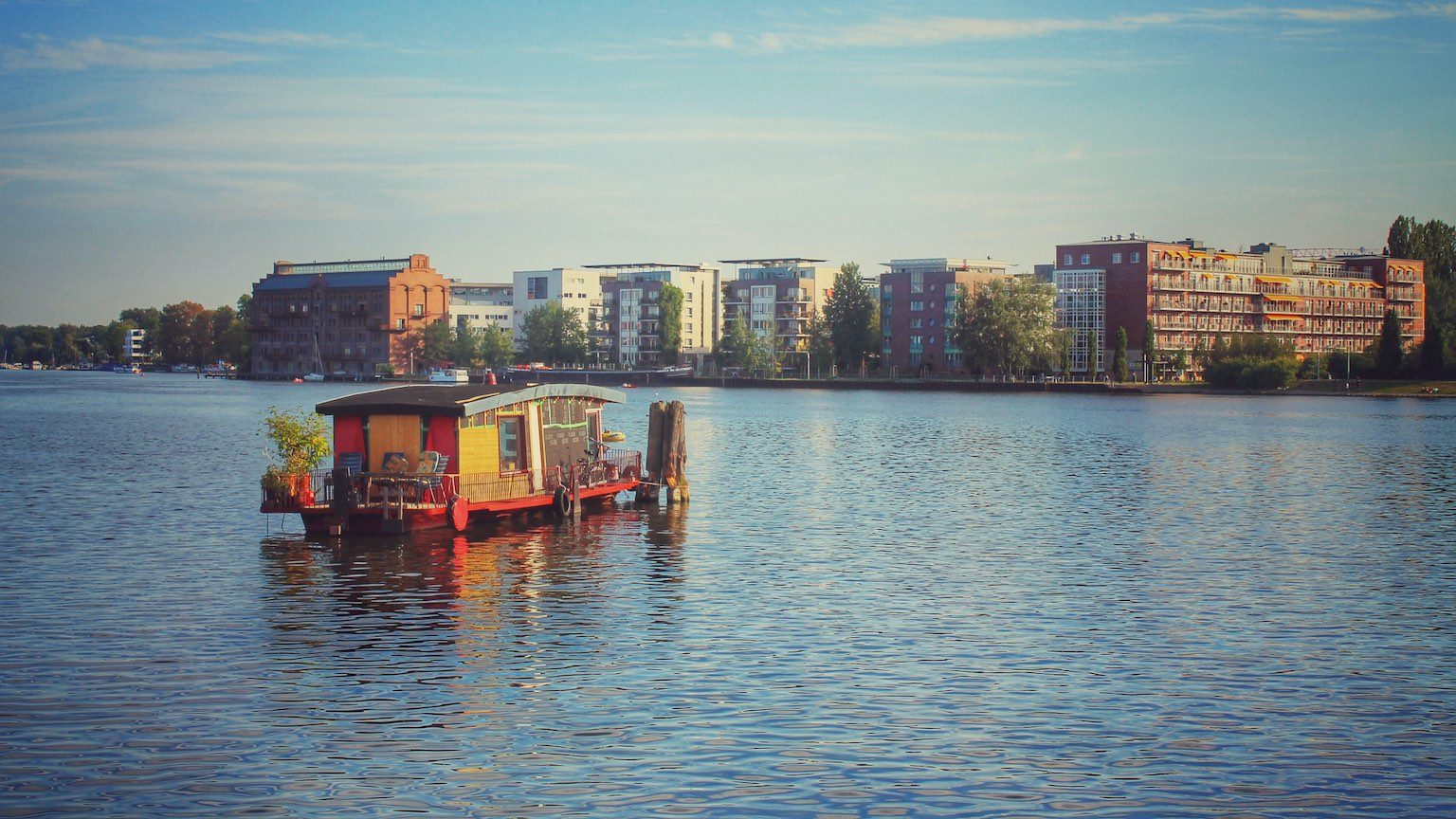 Houseboat moored in the middle of a river with view of the city on the shore.