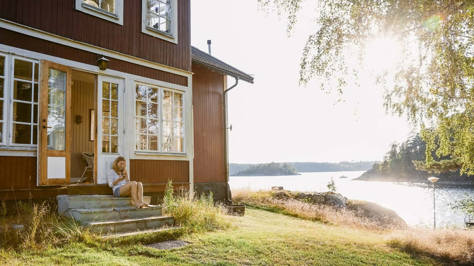 Woman sitting on front steps of a cabin by a lake in the sunshine.