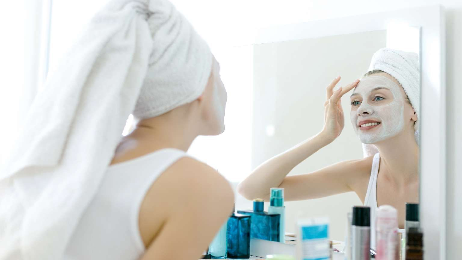 Woman applying face mask makeup looking in mirror and smiling.