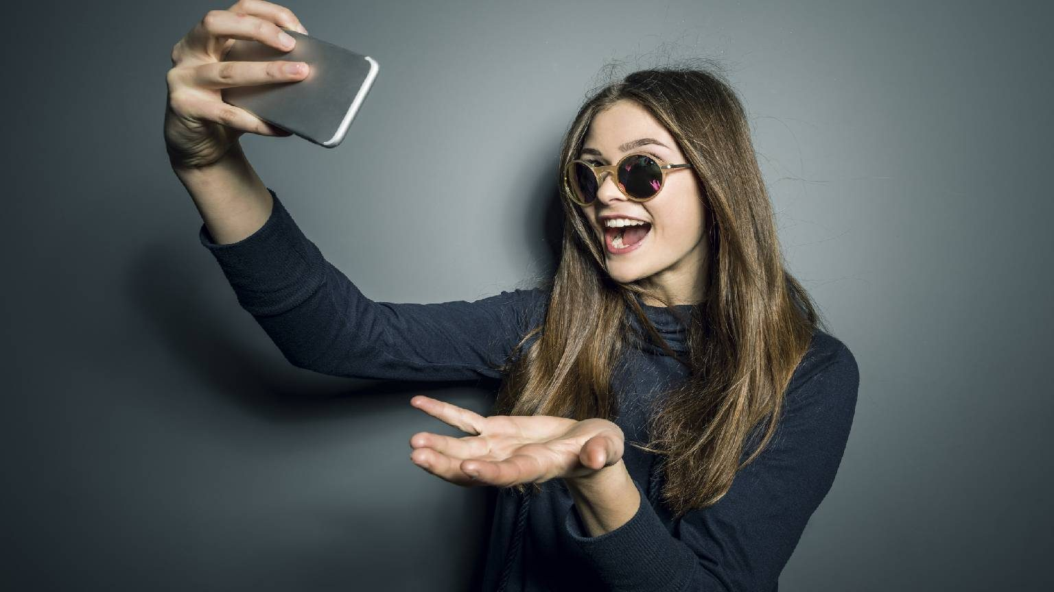 Girl with sunglasses smiling and taking selfie on cell phone.