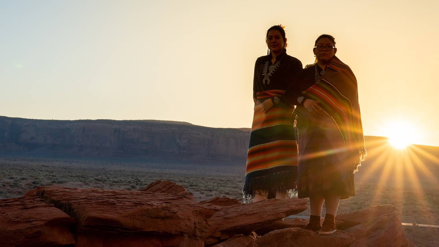 Two Indigenous women standing on a mesa with a sunset in the background.