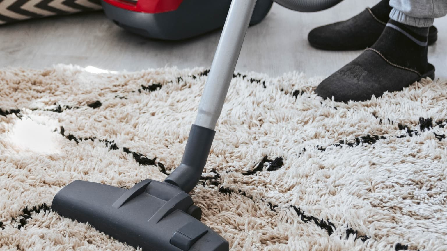 man cleaning carpet using a vaccum