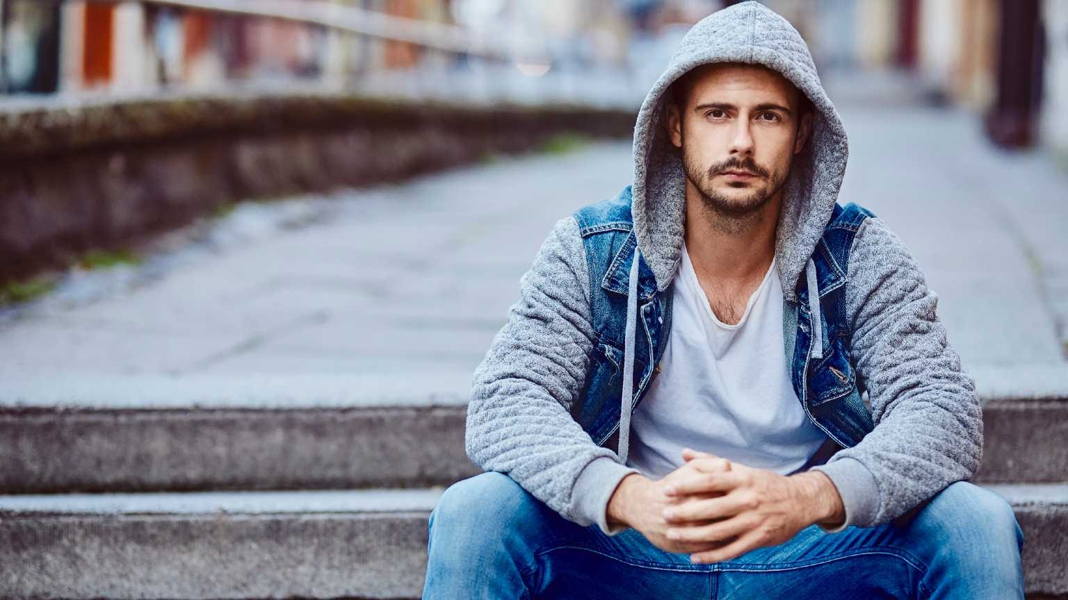 Serious man in hooded jacket sitting on stairs