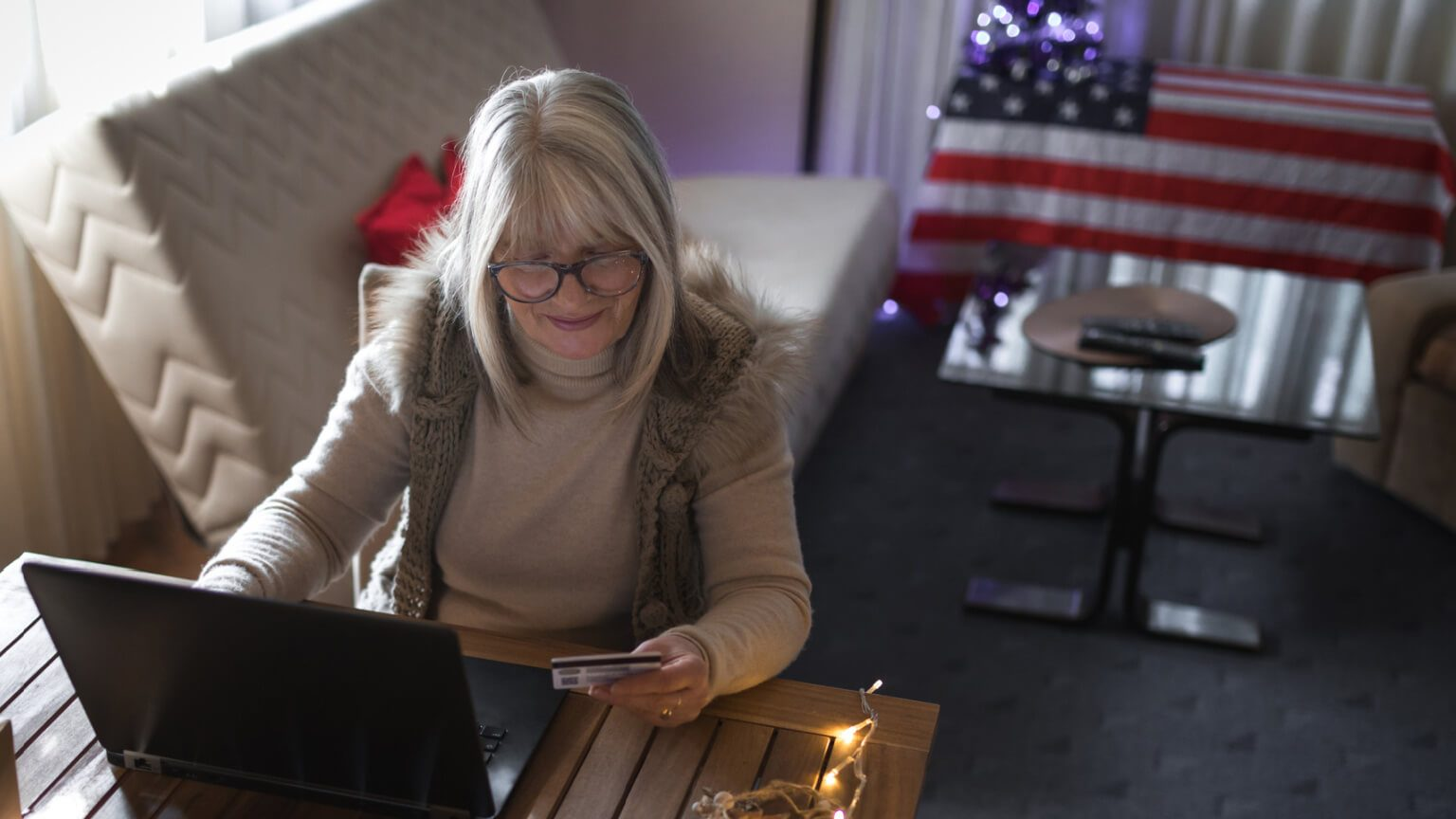 woman making a donation on her laptop with an american flag in the background