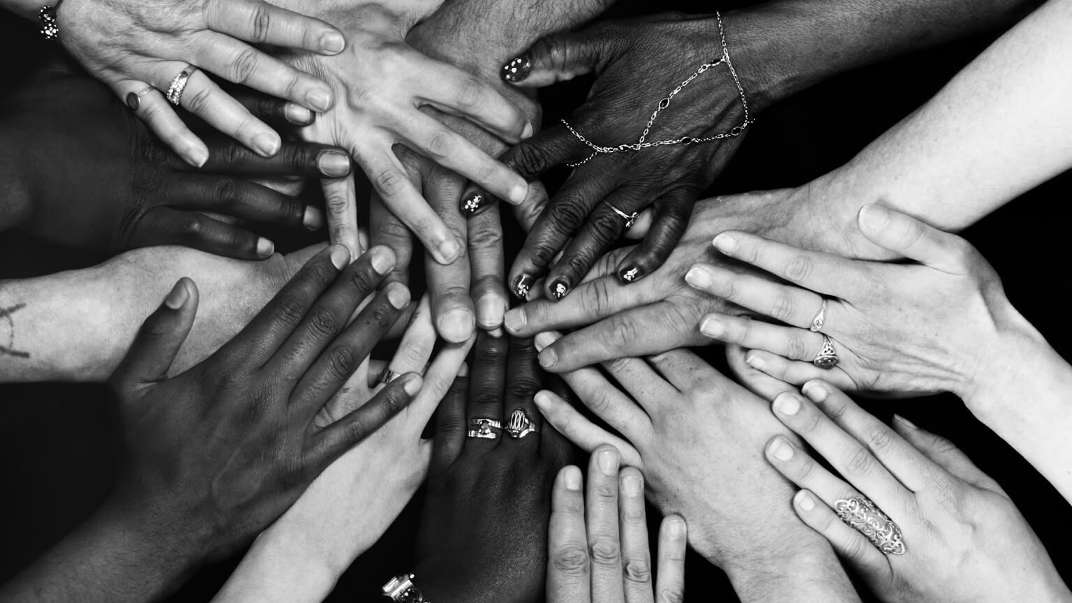 a black and white photo with multiple hands of all ethnicities signifying equality