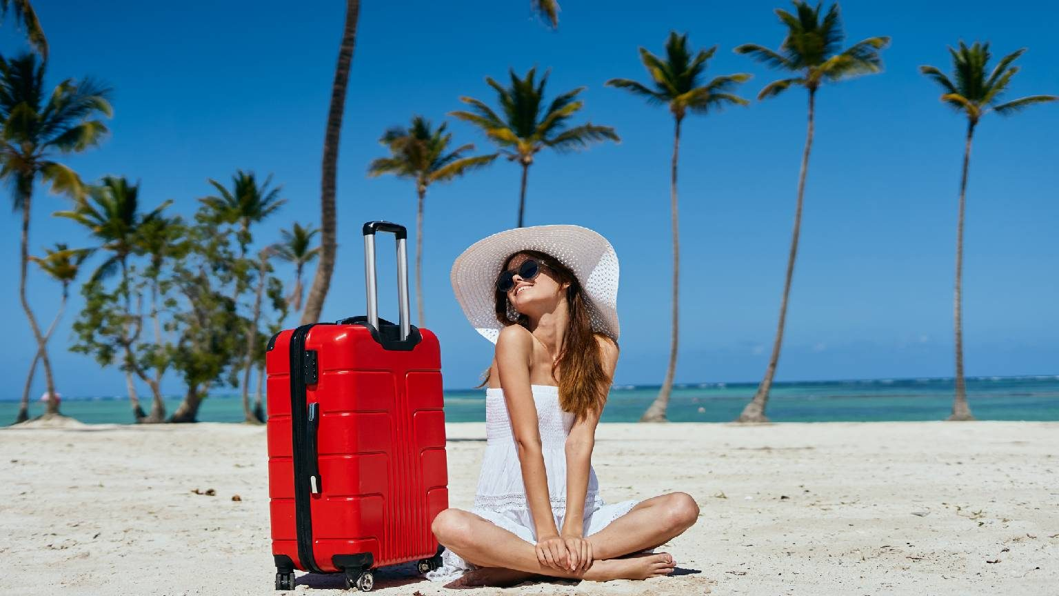 Woman smiling in white dress next to red suitcase on a sunny beach with palm trees in the background.