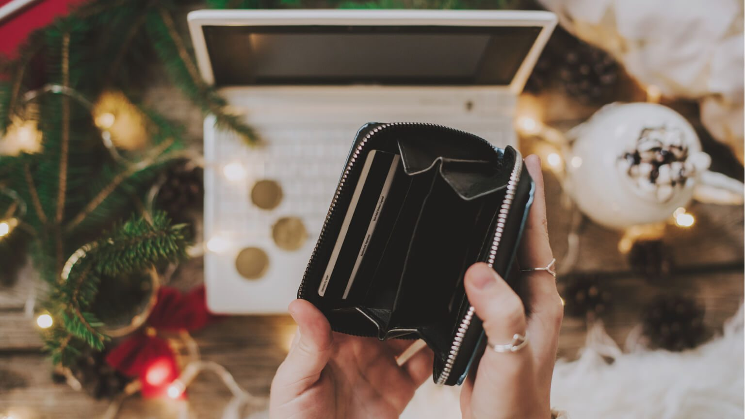 person holding an empty wallet over a white laptop in a Christmas setting