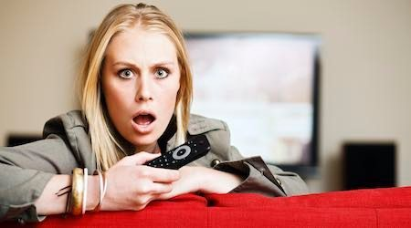 Horrified blonde babe holding remote control looks round from television