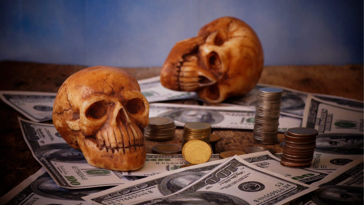 picture of fake skulls on top of 100 dollar bills and stacks of coins