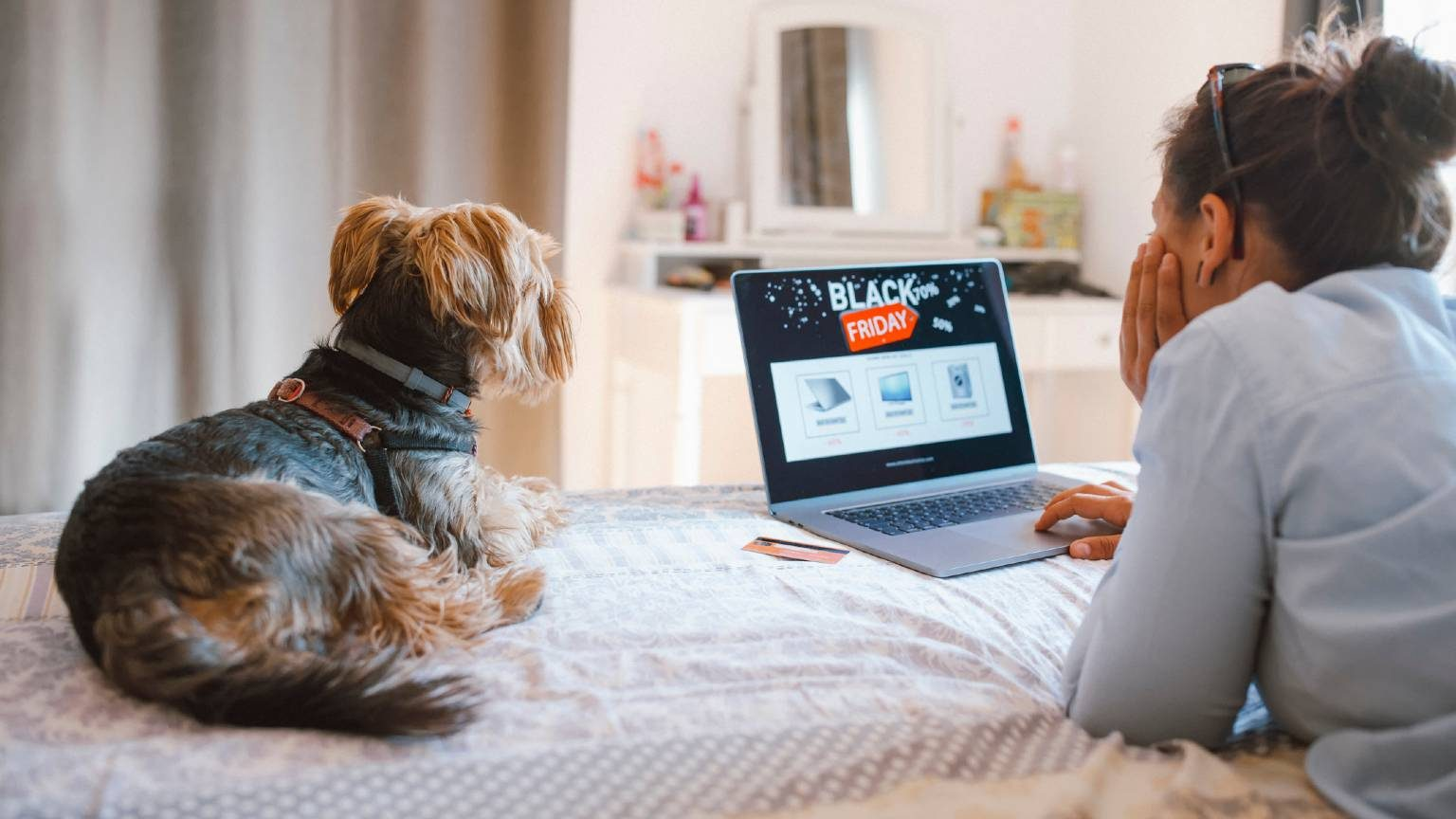Woman is buying electronics online at Black Friday while relaxing at the bed with her dog