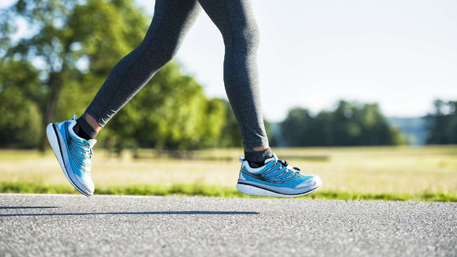 Woman running on road wearing blue running sneakers.