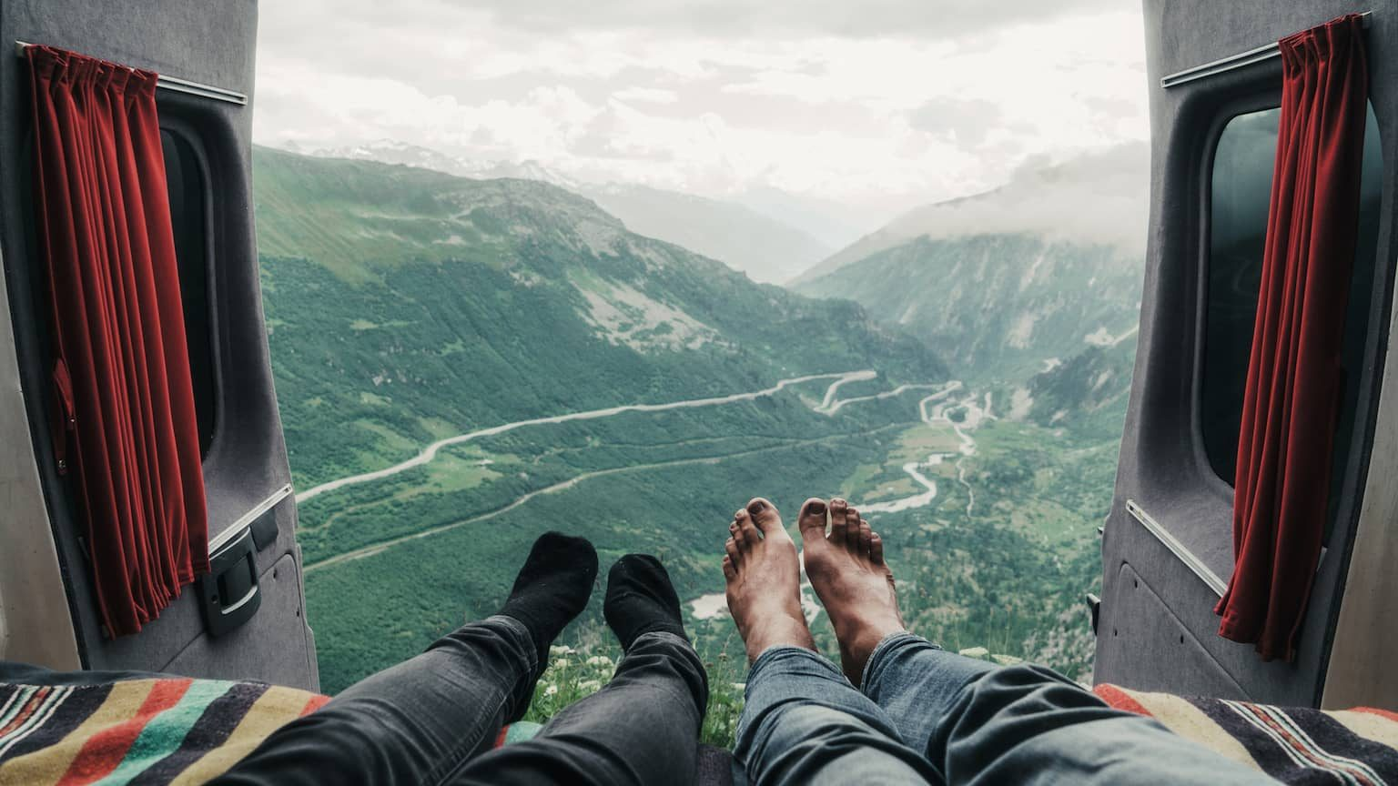 Couple sitting in the back of an RV, with their feet hanging out over a beautiful mountain view.