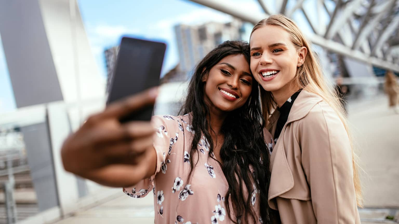Two young women smiling at a phone while taking a selfie with straight teeth