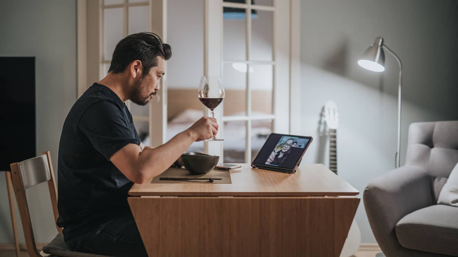 Man in his 30s sitting at his kitchen table with a glass of wine on a virtual date — talking to a woman on his tablet