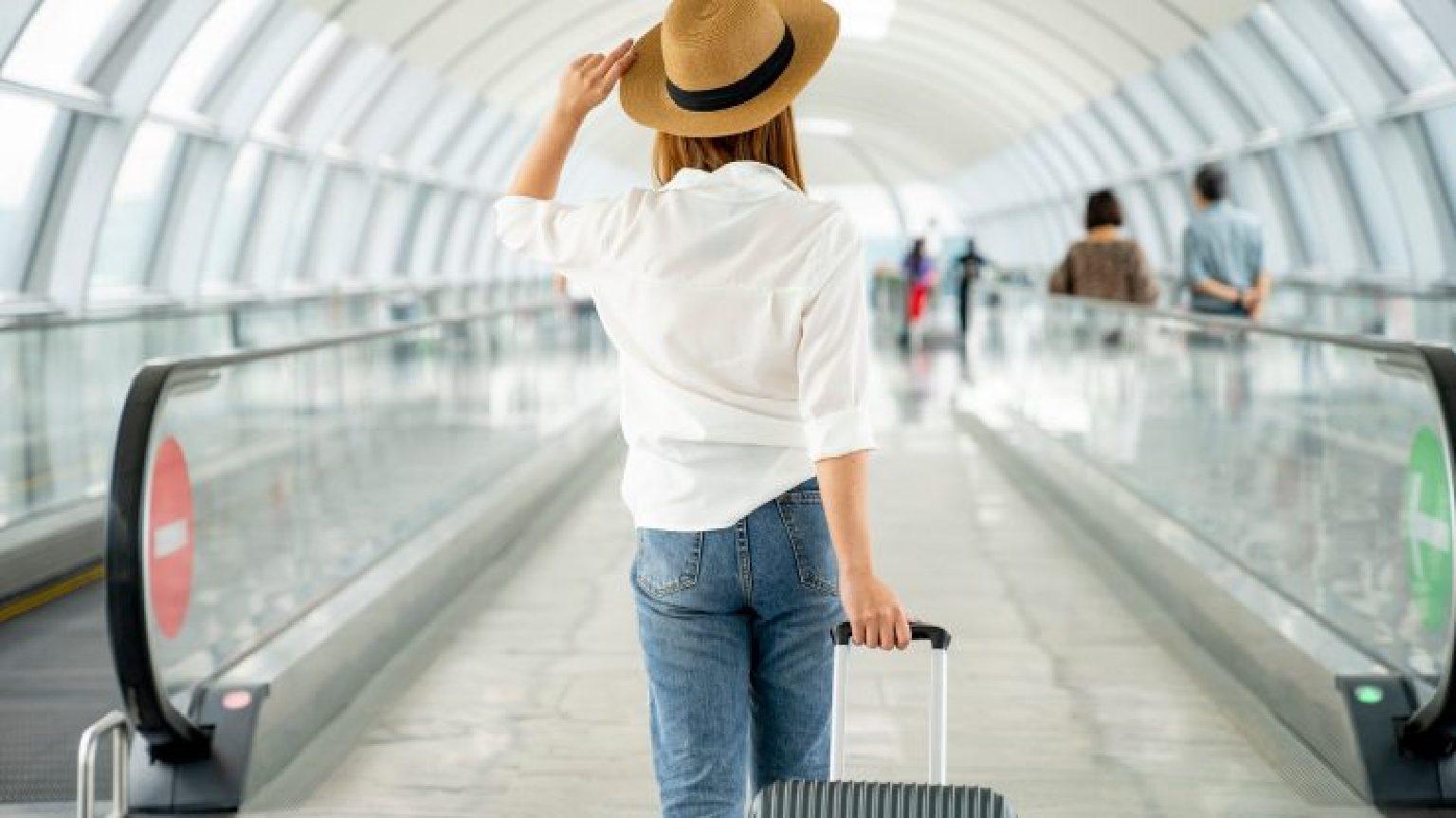 Traveler walking through airport with suitcase