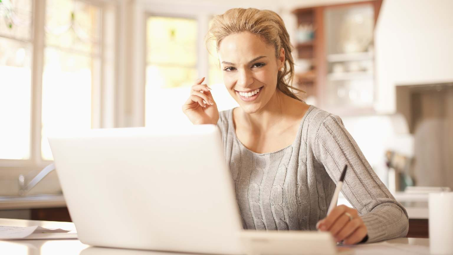 Smiling woman at home using laptop