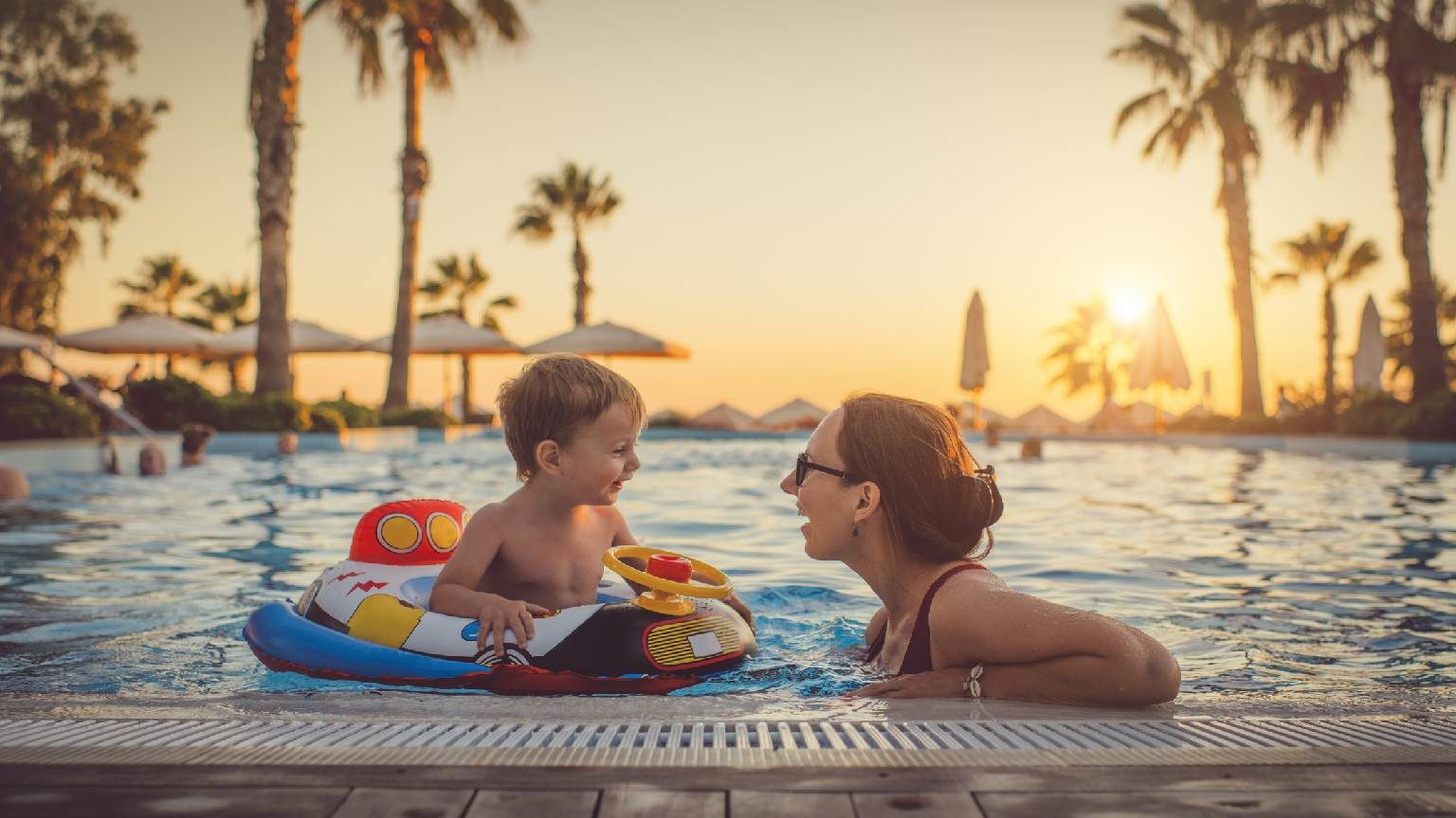 Woman playing with her son having fun at hotel pool at sunset