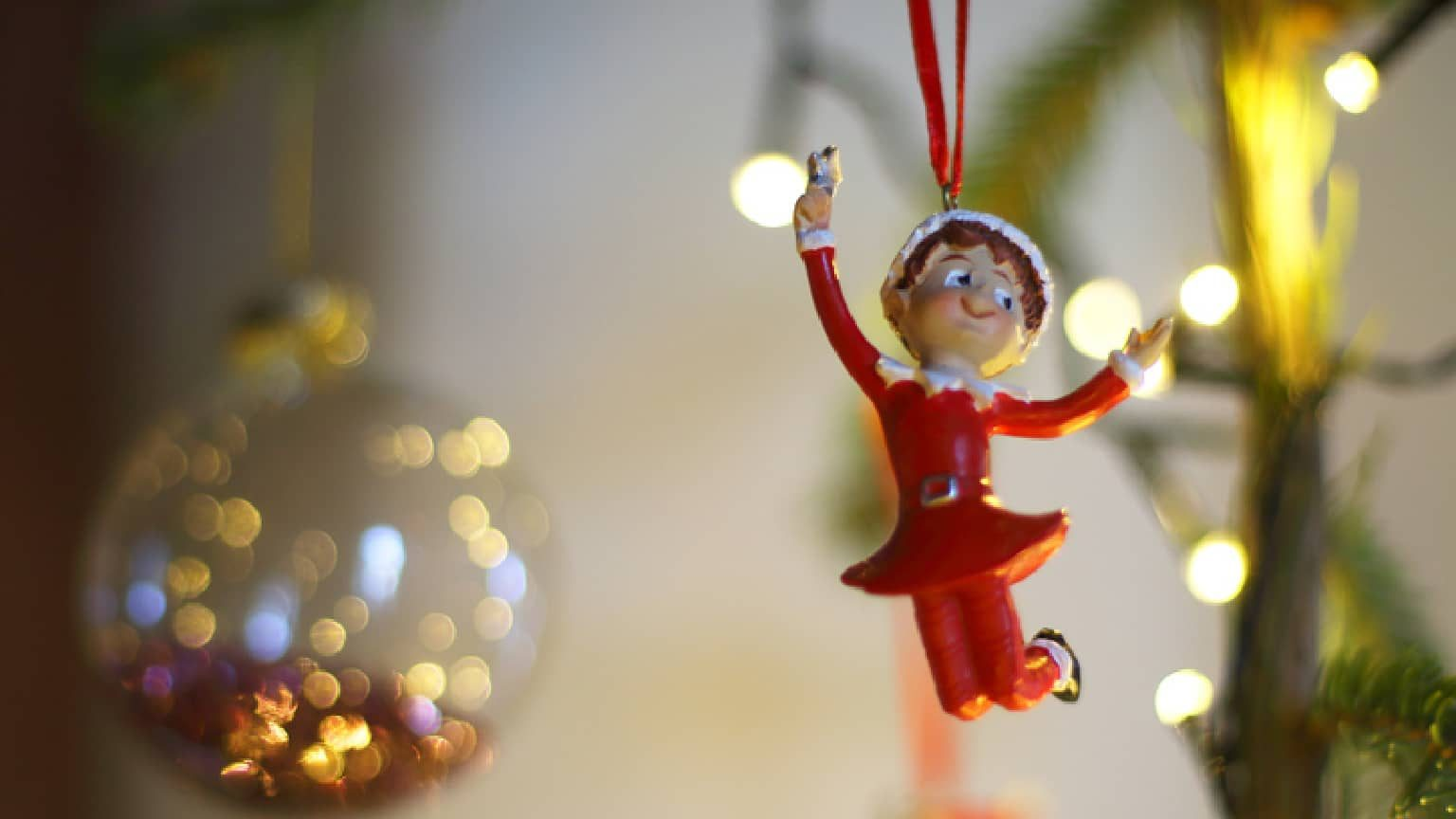 an elf on the shelf ornament hanging on a Christmas tree
