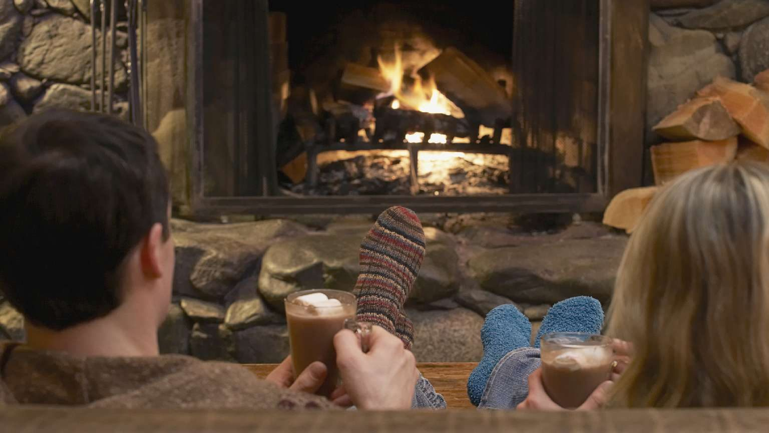 Couple relaxing in front of a roaring fire in a winter cabin.
