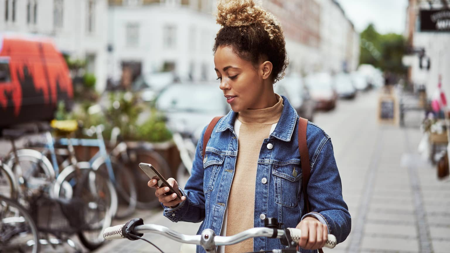 Young woman on bike, looking at her smartphone.