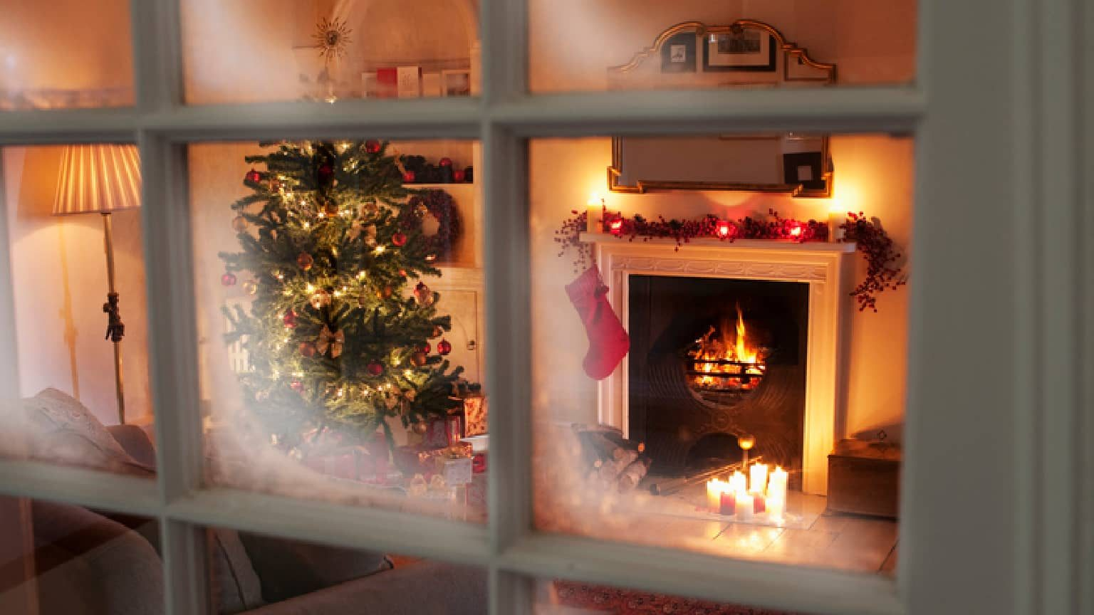 a home decorated for Christmas with a fireplace lit