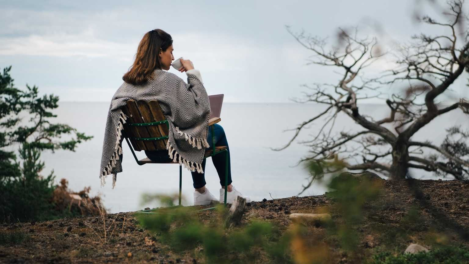 Rear view of woman drinking coffee while sitting with laptop on chair against lake